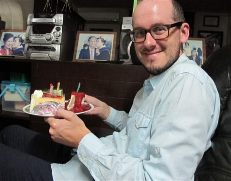 Robert on his birthday, in the comfy chair, surrounded by pictures of his Thai family