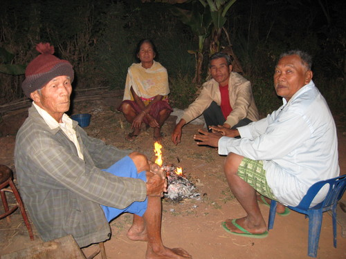 Elderly Villagers sit by fire at night to keep warm