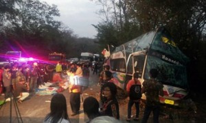 Thai rescue workers stand by bodies of victims of a bus accident on a road in Prachinburi province, east of Bangkok, early on February 28, 2014.  At least 15 people, including 13 children, were killed when a bus carrying students on a trip to the seaside collided with a lorry in eastern Thailand on February 28, police said.