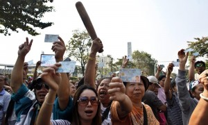 Protesters demanding the right to vote, hold up their identity cards and a rolling pin (C) before a minor clash between supporters and opponents of Thailand's government outside a polling station in central Bangkok, February 2, 2014. Thailand went to the polls under heavy security on Sunday in an election that could push the divided country deeper into political turmoil and leave the winner paralysed for months by street protests, legal challenges and legislative limbo. REUTERS/Nir Elias