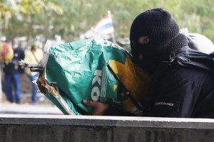 An anti-government protester shoots his rifle, hidden it inside a sack, toward pro-government protesters during clashes in Bangkok February 1, 2014. REUTERS/Nir Elias