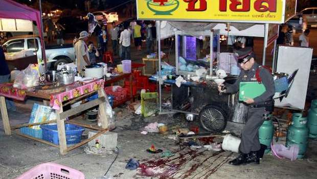 Thai police officer inspecting a pile of blood after an attack on anti-government protesters at a noodle stall near their rally stage in Khao Saming district, Trat province,