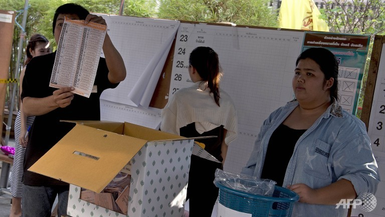 Election commission officials display ballot papers to the media while counting votes at a polling station in Bangkok
