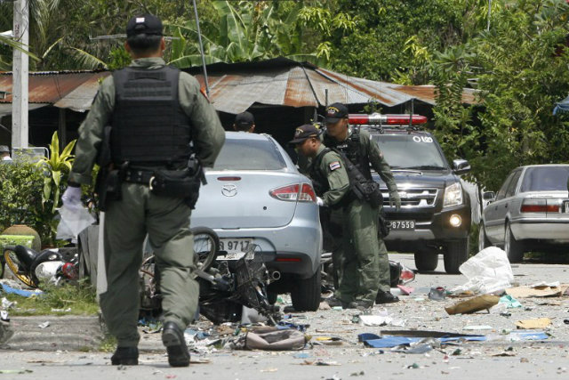 Members of the bomb squad inspects the site of bomb blast, detonated by suspected separatist militants