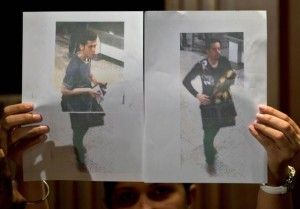 A Malaysian police official displays photographs of the two men who boarded the Malaysia Airlines MH370 flight using stolen European passports