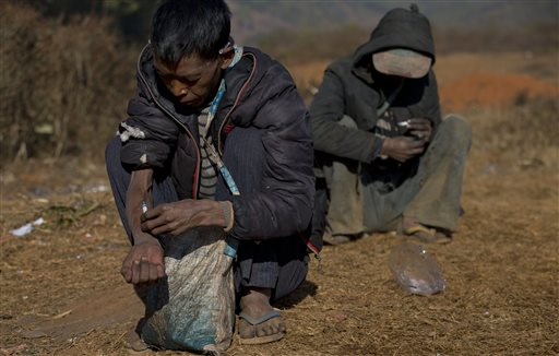 addicts use needles at a cemetery in Nampatka village, northeastern Shan State, Myanmar. Every morning, more than 100 heroin and opium addicts descend on the graveyard to get high
