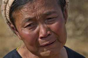 Daw Li weeps before the graves of her two oldest sons, both victims of heroin overdoses, at Nampatka village cemetery, northeastern Shan State, Myanmar.