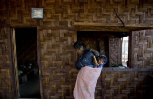 Hpatau Ma Hkang, a volunteer who was addicted to heroin for 30 years before his rehabilitation in 2013, carries two-year-old boy Tsaw Tsaw. The boy's patents are both going through a drug addiction rehabilitation program run by the Kachin Baptist Community at Nampatka Village, Northern Shan State, Myanmar
