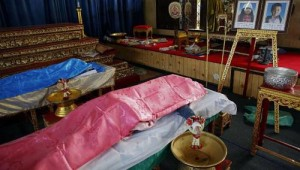 The bodies of a pair of siblings killed in a bomb blast near an anti-government protest site on Sunday being prepared for a funeral at a Buddhist temple