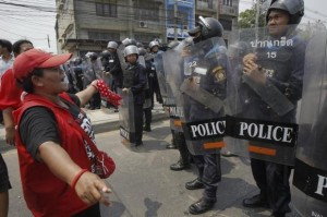 Members of the pro-government red shirt movement face riot police outside the offices of the National Anti-Corruption Commission in Nonthaburi province, on the outskirts of Bangkok