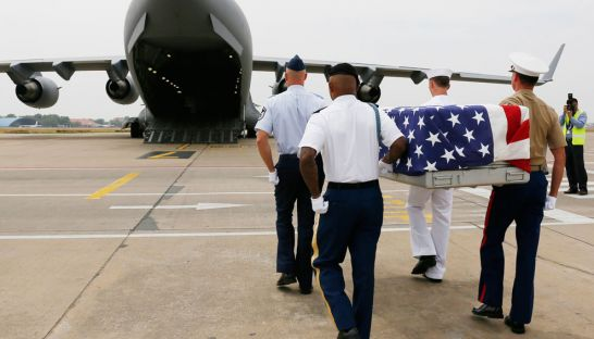US soldiers carry a coffin across the tarmac at Phnom Penh International Airport yesterday as part of a repatriation ceremony for remains believed to be those of US soldiers from the Vietnam War