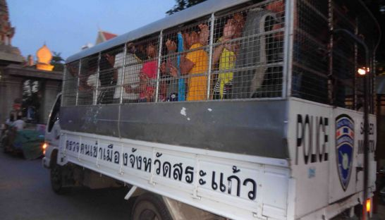 Detained migrant workers are transported in a Thai police vehicle at the Poipet International Checkpoint on the weekend after being detained by Thai security forces