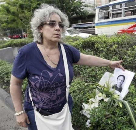 Isabella Polenghi, younger sister of Italian photographer Fabio Polenghi who was killed as troops forcibly suppressed an anti-government protest in Bangkok in 2010, places a flower and the copy of his portrait near the site where her brother was killed to commemorate the second  anniversary in Bangkok Saturday, May 19, 2012. On Saturday, Red Shirt supporters gathered in central Bangkok to peacefully mark the anniversary. (AP Photo/Sakchai Lalit)