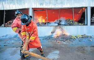 Firefighters try to control the blaze at a Sri Samai warehouse on Siroros Road in Yala municipality. The fire followed a bomb explosion at the premises. A total of four targets were hit by bomb attacks...