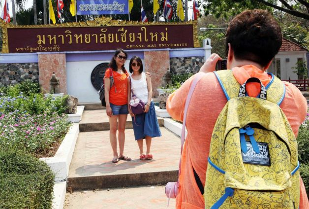 Chinese tourists pose for a photograph at the main entrance to Chiang Mai University in Chiang Mai province,