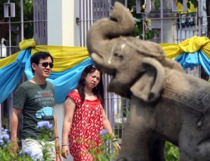 Chinese tourists walks past a stone carving elephant as they enter for a tour at Chiang Mai University