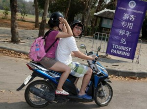Chinese tourists ride on a motorcycle past a parking sign erected inside Chiang Mai University