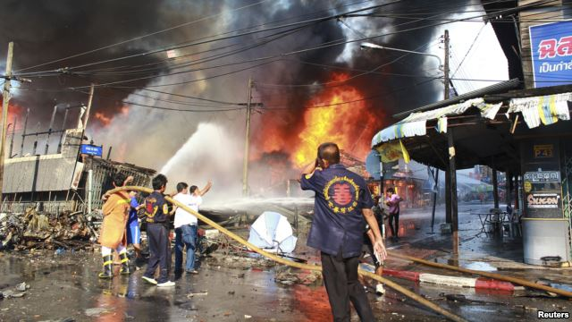 Rescue workers extinguish a fire at the site of a bomb blast in southern Thailand's Yala province