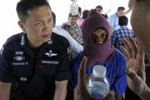 Police Major General Thatchai Pitaneelaboot (L) listens as a Rohingya trafficking victim leads a police unit to a camp where he was detained in Satun, southern Thailand