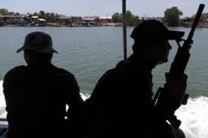 Armed police provide security to Police Major General Thatchai Pitaneelaboot as they sail up a river in towards a trafficking camp in Satun, southern Thailand