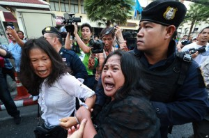 A woman tries to help as an anti-coup protester is detained by a Thai police officer during a street protest in Bangkok,