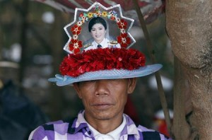 "A member of the pro-government ""red shirt"" group wearing a hat with a picture of ousted Thai prime minister Yingluck Shinawatra during a rally in Nakhon Pathom province on the outskirts of Bangkok May 22, 2014."