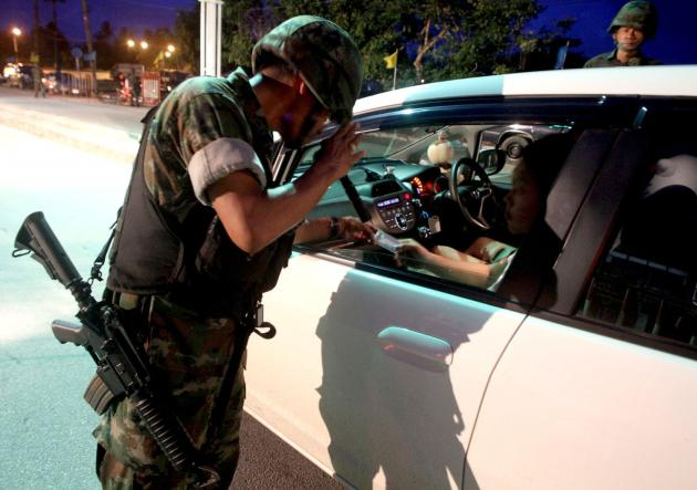 Thai Soldier inspects ID of driver at road block
