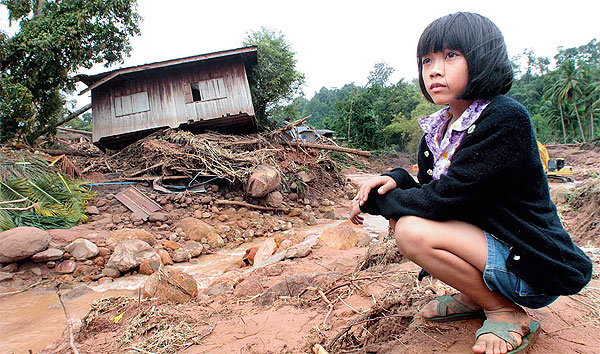 A girl stares at the place where her house sat until it was swept away by a flash flood that also triggered a mudslide