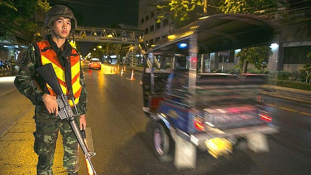 A Thai soldier stands guard at a checkpoint after a curfew started