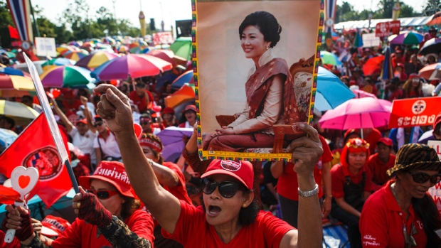 """A member of the pro-government """"red shirt"""" group holds a picture of ousted Thai prime minister Yingluck Shinawatra during a rally in Nakhon Pathom province on the outskirts of Bangkok, May 10, 2014."""