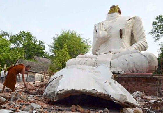 A Thai Buddhist monk removes debris and remains of a collapsed Buddha statue damaged by the 6.3 magnitude earthquake at Wat Udom Waree temple in Phan district, Chiang Rai province,