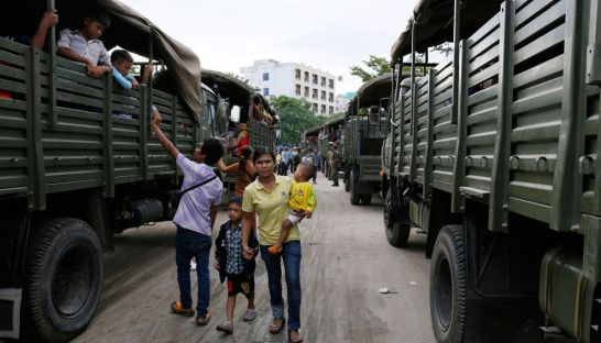 A Cambodian migrant worker with her children walks past a queue of military transport trucks at the Poipet border town last week