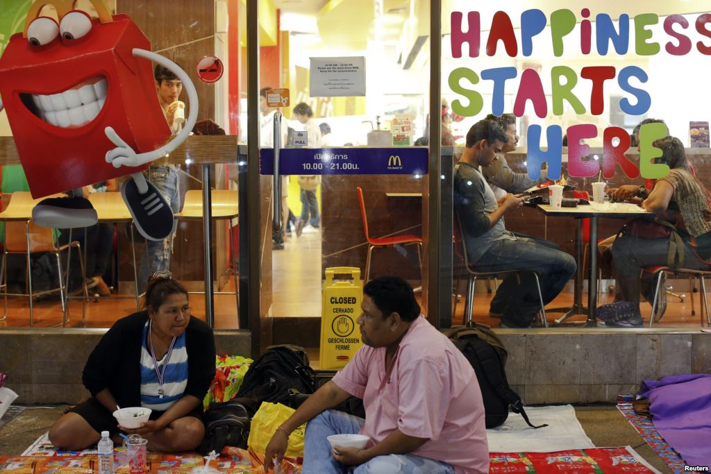 Anti-government protesters eat dinner outside a McDonald's restaurant in central Bangkok.