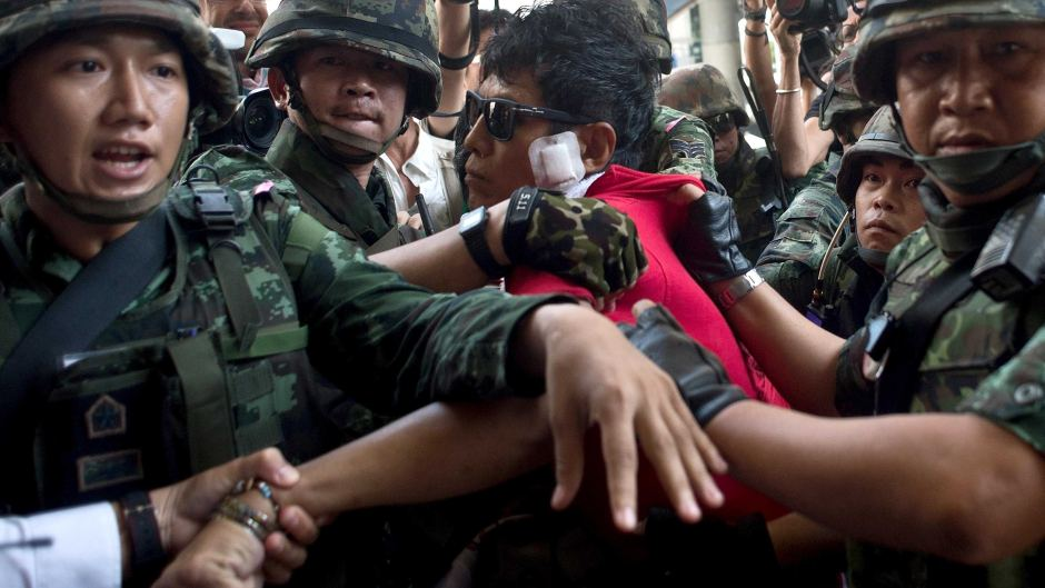 Thai soldiers take away an alleged Red-Shirt protester ahead of a planned gathering.