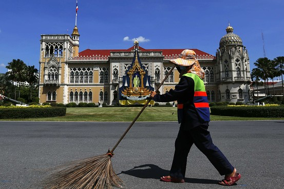 A cleaning woman sweeps in front of the Government house, the complex where offices of country's prime minister and other officials are located, in Bangkok on Saturday. Reuters