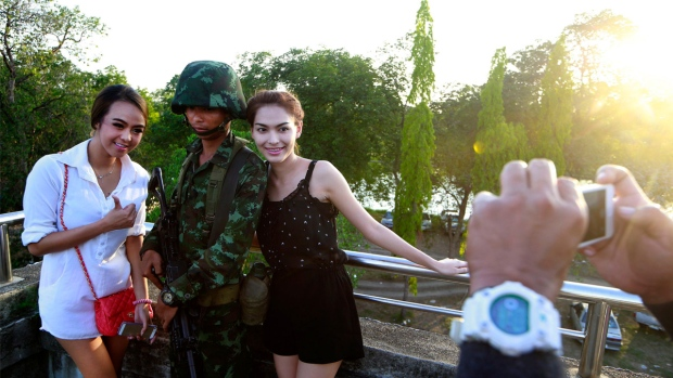 Passersby have their photograph taken with a Thai soldier on the outskirts of Bangkok, Thailand. AP Photo/Wason Wanichakorn