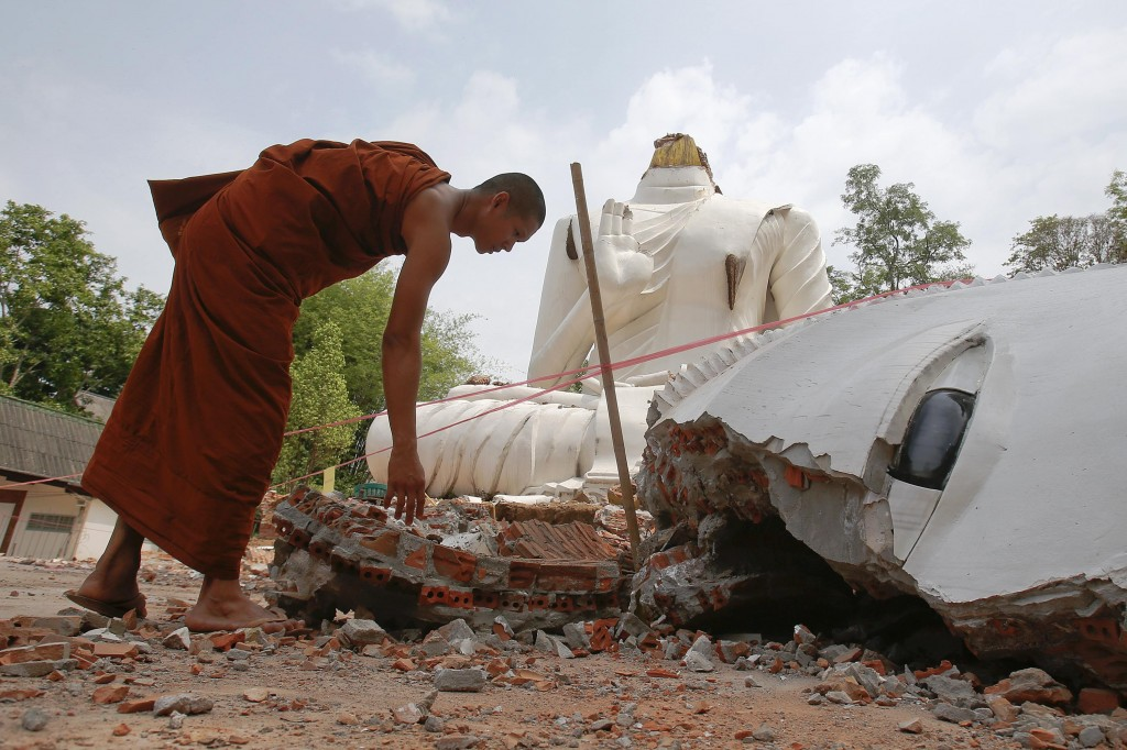 A Buddhist monk checks a Buddha statue that was damaged by an earthquake at the Udomwaree temple in Chiang Rai, in northern Thailand May 6, 2014.