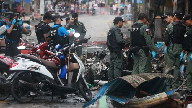 Members of a bomb squad inspect damaged vehicles after a bomb explosion outside a hotel at Betong district in Thailand's southern province of Yala