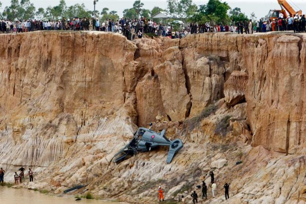 Soldiers use a crane to lift an aft section of a helicopter retrieved from a pond following its crash in Prey Sar village at the outskirt of Phnom Penh, Cambodia, Monday, July 14, 2014