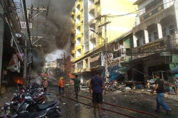 Firemen trying to stop the flames from spreading at the site where a car bomb exploded outside a hotel at Betong district in Thailand's southern province of Yala on July 25, 2014.