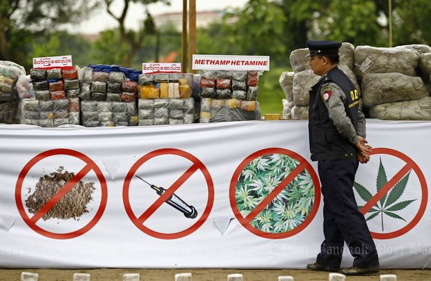 A Myanmar policeman walks past a pile of drugs prior to a 'Destruction Ceremony of Seized Narcotic Drugs' to mark International Day against Drug Abuse, in Yangon, Myanmar, on June 26, 2014. (EPA photo)