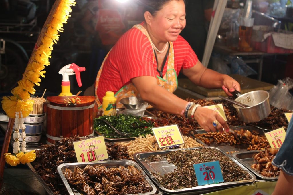 A woman sells fried insects at a stand in Chiang Rai
