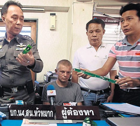 Anton Lilin, 30, a Russian national, is taken before reporters following his arrest on Monday in the Ramkhamhaeng area on charges of ATM skimming. THANARAK KHUNTON