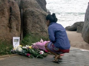 A Thai villager lays flowers during a memorial service for two murdered British tourists at the crime scene on a beach of Koh Tao resort island