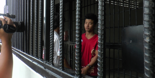 A cameraman films the two murder suspects behind bars at the detention centre on Koh Samui on Saturday. (Photo: Supapong Chaolan)