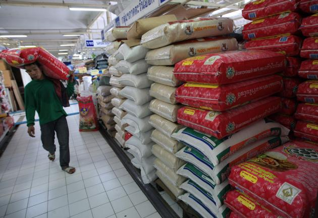A worker carries a bag of rice at a market in Bangkok