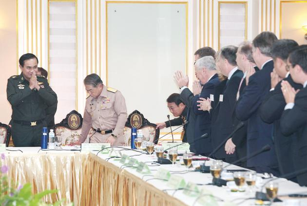 General Prayuth Chan-ocha gives a traditional greeting to foreign chamber of commerce members before a meeting at the Royal Thai Army Headquarters in Bangkok after Coup.