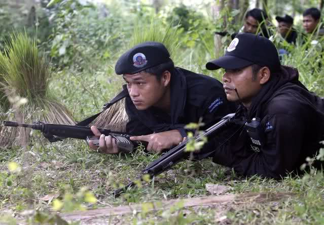 Thai soldiers take position following a gun battle with suspected Muslim insurgents in Pattani province