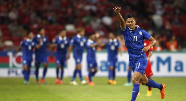 Thailand's Mongkol Thossakrai (right) salutes Thai supporters after scoring his team's first goal against Singapore during their Suzuki Cup Group B match at the National Stadium in Singapore - See more at: http://www.tnp.sg/sports/singapore-lose-2-1-thailand-suzuki-cup-opener#sthash.mVdDLxsK.dpuf