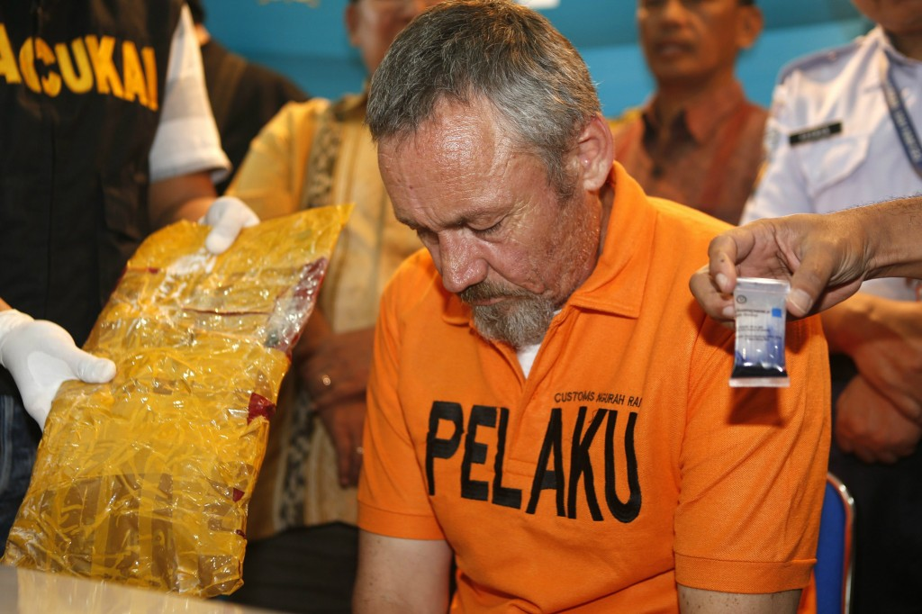 Antony Glen De Malmanche of New Zealand sits as evidence is placed next to him by customs security during a press conference at the customs office in Denpasar on Bali island.